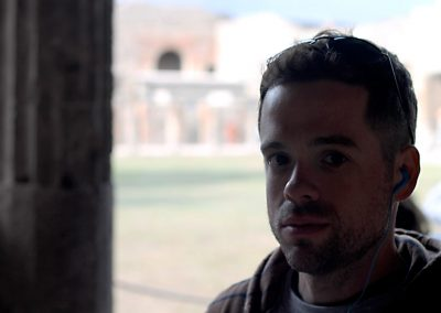 Mike in a dark hall with Pompeii behind him.