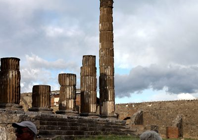 Grey clouds loom over the ruined columns of Pompeii.
