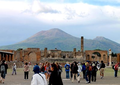 This was once the bustling center of Pompeii. The ruins are shadowed by the looming volcano as tourists walk the square.