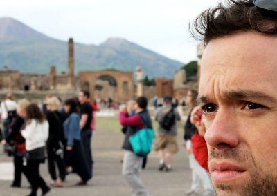 Mike is listening to the tour guide talk about the events of Pompeii's destruction with Vesuvius looming in the background.