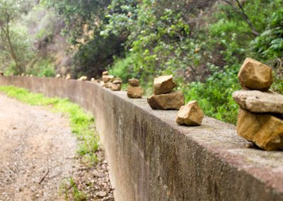 Totems and trail markers. These rock stacks lined an entire wall down the path to the creek.